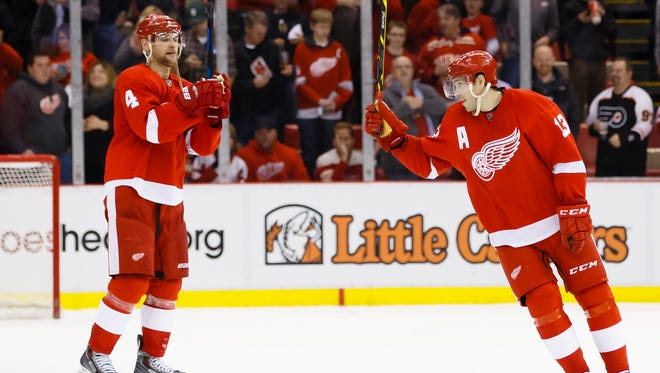 Red Wings defenseman Jakub Kindl (4) and enter Pavel Datsyuk (13) salute the fan after their game against the Philadelphia Flyers at Joe Louis Arena. Detroit won 5-2.