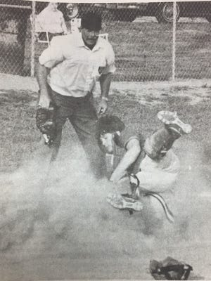 Union County catcher Jason Walker was in a cloud of dust as a Henderson County player slid into home during a game in May 1989.