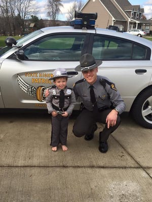 Trooper Adrian Wilson poses with 2-year-old Jibsen while delivering a special gift for the boy last week.