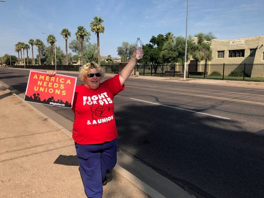 "Nora Whipple, a fast-food worker in Phoenix, holds up an ""America Needs Unions"" sign during the gathering near 10th Avenue and Van Buren Street on Monday, Sept. 4, 2017, during Labor Day."
