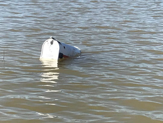 A mailbox is almost totally submerged by rising flood
