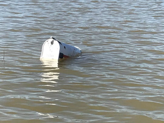 A mailbox is almost totally submerged by rising flood waters in the Beals area