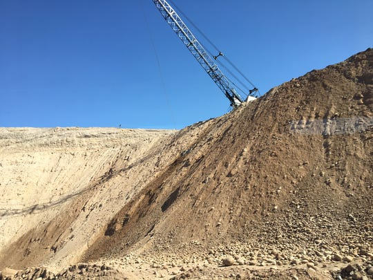 A crane hangs over the sand and gravel pit at Vulcan