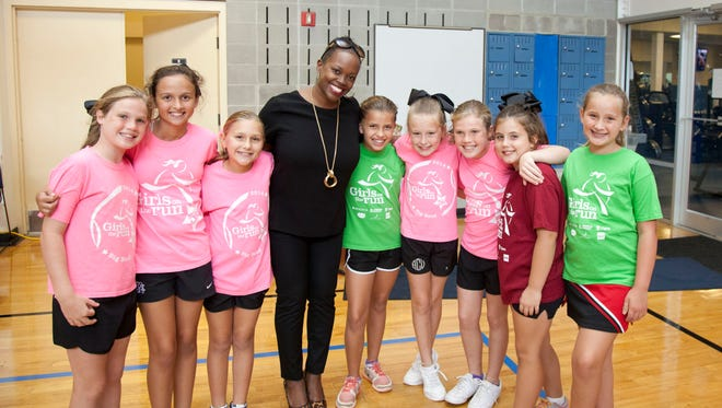 R Jai Gillum poses with Girls On The Run participants.