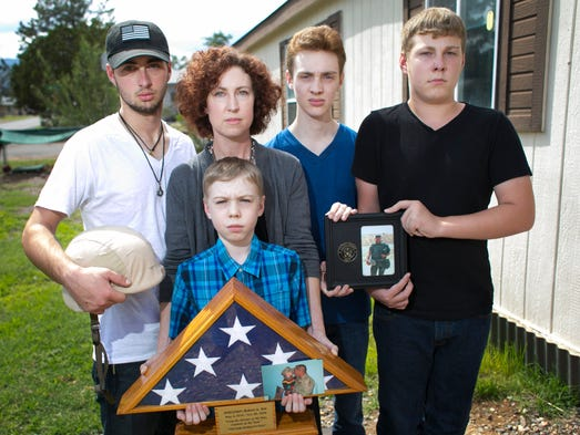 Victoria Yett, 39, is seen with her four sons (from left)  Zach, 19; K.J., 10; Kyal, 17; and Zane, 14; all holding a photograph of their father, Robert Yett, and other military items associated with him at their home in Cottonwood on Aug. 12, 2014. After serving with the U.S. Navy during several tours in Iraq and Afghanistan, Robert Yett committed suicide in November 2010. He was trying to seek treatment for his post traumatic stress disorder from the VA.