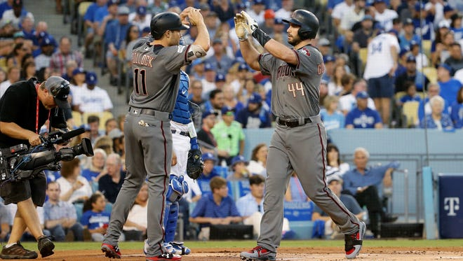 Arizona Diamondbacks A.J. Pollock high-fives Paul Goldschmidt after Goldschmidt hit a 2-run home run against the Los Angeles Dodgers in the 1st inning during Game 2 of the NLDS on Oct. 7, 2017 at Dodger Stadium in Los Angeles, California.