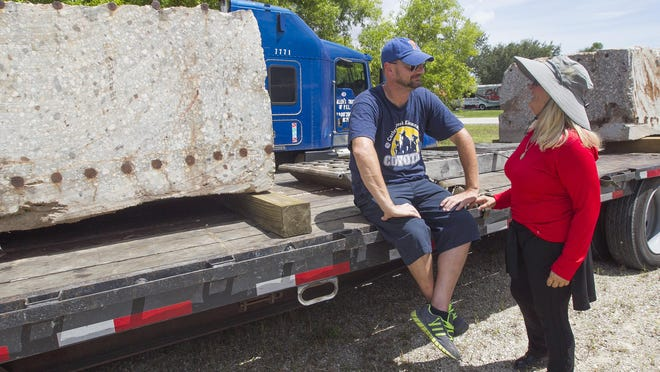 Truck driver Ralph Tutak and local artist Sandra Priest talk near 15,000 lb. concrete slurry wall pieces from Ground Zero in New York Wednesday in Fort Myers. Priest will turn the blocks into works of art.