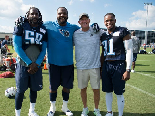 Erik Walden (58), defensive end Jimmy Staten (69), and MTSU coach Rick Stockstill and safety Kevin Byard (31), pictured from left, pose for a photo after the first practice of the 2017 Tennessee Titans training camp in 2017.