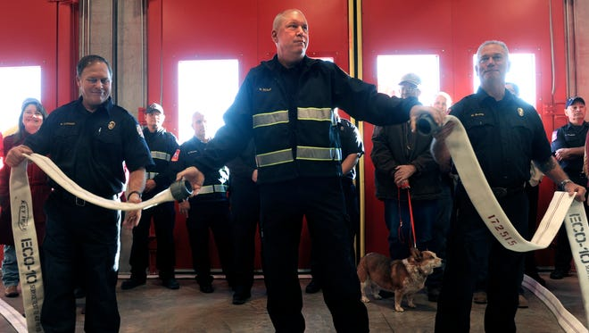 Rather than cut a ribbon, Abilene Fire Department Captain Randy Scalf holds the two halves of a hose after ceremoniously uncoupling it with the assistance of Walt Clemmer (left) and Mark Bland Friday Dec. 15, 2017 at the new Station No. 4. The new station is located at 3750 Grape Street, north of Interstate 20.