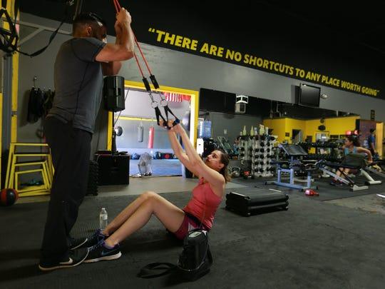 Trainer Gabino Gonzalez watches Dima Azzam performs sit-ups at the Metamorphosis Gym..