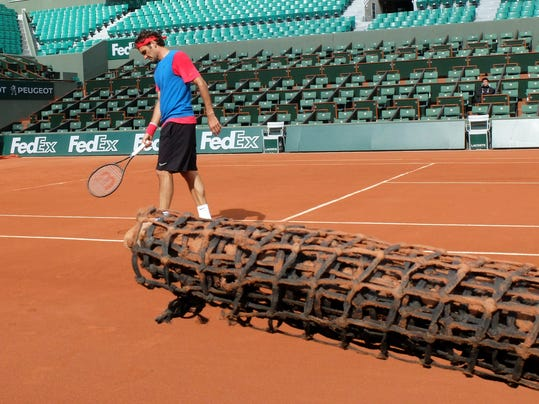 Switzerland's Roger Federer walks on the court during a training at the Roland Garros stadium in Paris, Friday, May 23, 2014. The French Open tennis tournament will start Sunday.  (AP Photo/Bertrand Combaldieu)