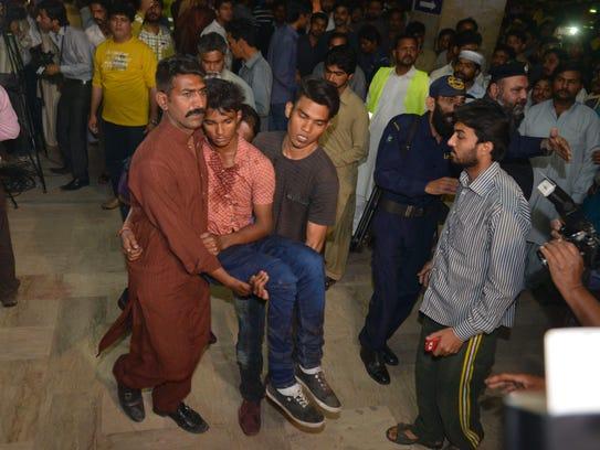 Pakistani relatives carry an injured bomb blast victim.