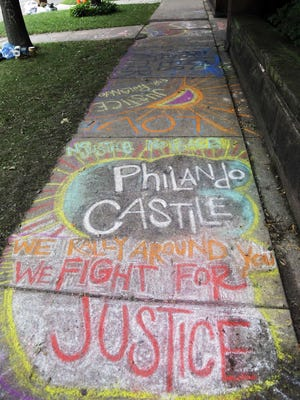 A chalk tribute to Philando Castile marks a sidewalk across the street from the governor's residence as demonstrators gather outside the governor's residence July 8 in St. Paul where protests continue over the shooting death by police of Castile after a traffic stop July 6 in Falcon Heights.