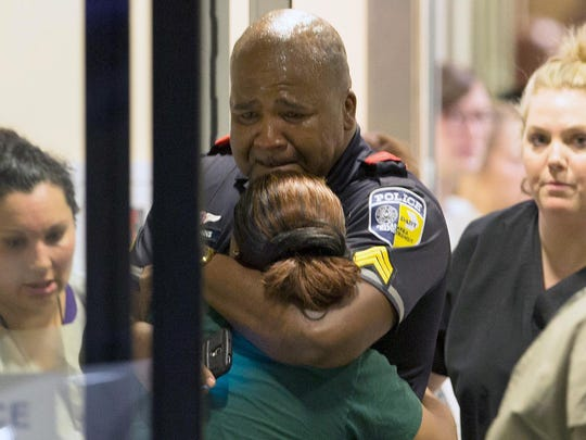 A Dallas Area Rapid Transit police officer is comforted Thursday at a Dallas hospital's emergency-room entrance.