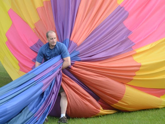 Larry Coan of Livonia squeezes the air from his balloon