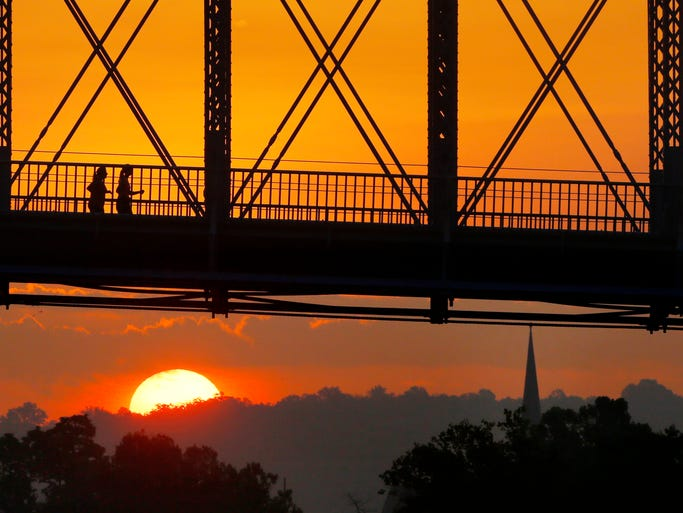 Runners cross the John A. Roebling Suspension Bridge at sunrise on Wednesday, August 27.