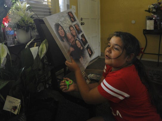 Jazlyn Fisher, 8, looks through family photos. Her