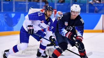 United States forward Ryan Donato (16) looks to play the puck in a hockey game against Slovakia.