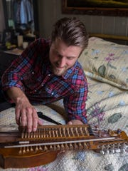 Swedish musician Roger Andersson checks out his nyckelharpa,
