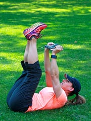Catherine Andersen,co-owner and personal trainer at Adventure Boot Camp in Milwaukee, demonstrates the straight leg crunch for the Tabata segment of the dorm and campus workout series.