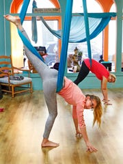 Samantha Orgman (front), 18, does the three-legged dog pose in the Aerial Yoga Foundation class at Reaching Treetops Yoga in Waukesha.