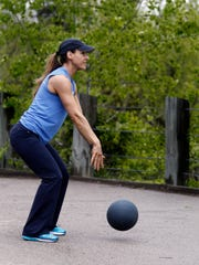 Catherine Andersen shows the ending position for the medicine ball slam exercise.