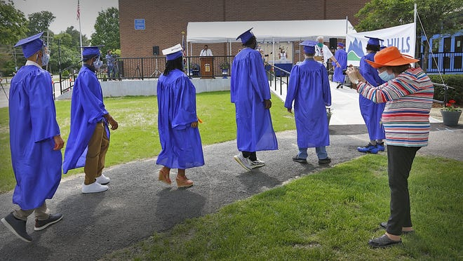 Blue Hills Regional Technical School students line up six feet apart while staffer Judy Bass takes a photo of the  graduating seniors on Tuesday.