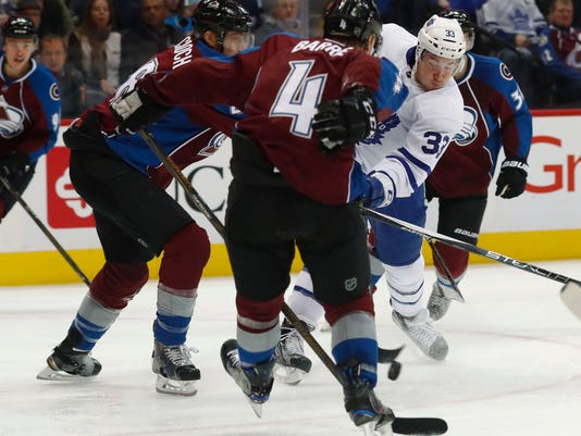 Toronto Maple Leafs center Frederik Gauthier, back, fires the puck between Colorado Avalanche defensemen Patrick Wiercioch, front left, and Tyson Barrie in the second period of an NHL hockey game Thursday, Dec. 22, 2016, in Denver. (AP Photo/David Zalubowski)