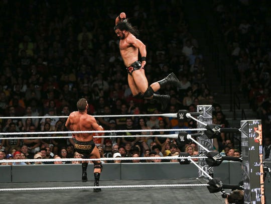 Drew McIntyre jumps off the top turnbuckle onto former