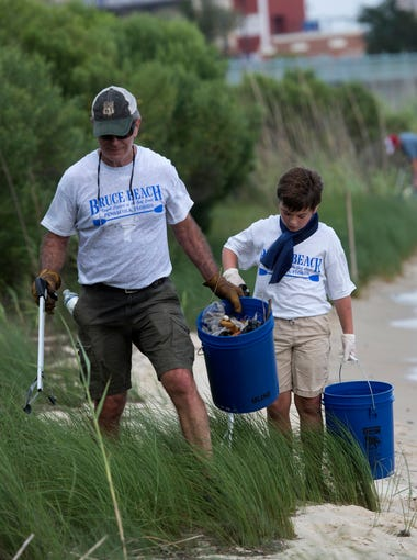 Dan Lindemann, and his grandson, Cooper, work together to help clean-up Bruce Beach on Wednesday, July 18, 2018. Lindemann is one of the co-organizers of the project.