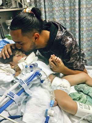 In this recent undated photo, released Monday, Dec. 17, 2018, by the Council on American-Islamic Relations in Sacramento, Calif., Ali Hassan kissing his dying 2-year-old son Abdullah in a Sacramento hospital. Abdullah Hassan, the son of a Yemeni woman who sued the Trump administration to let her into the country to be with the ailing boy has died.