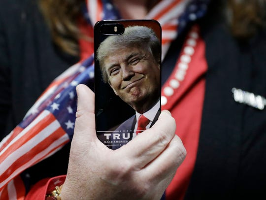 A woman holds up her cell phone before a rally with