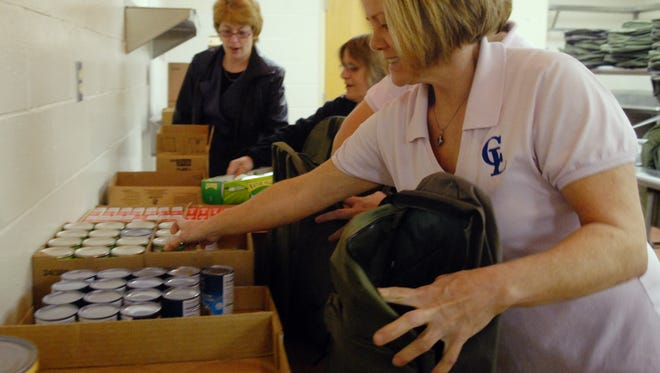Mary Norman packs a backpack with healthy food at Geiger Elementary in Croswell. The Community Foundation of St. Clair County is piloting a program in Algonac schools to serve older students and with a view to going year-round.