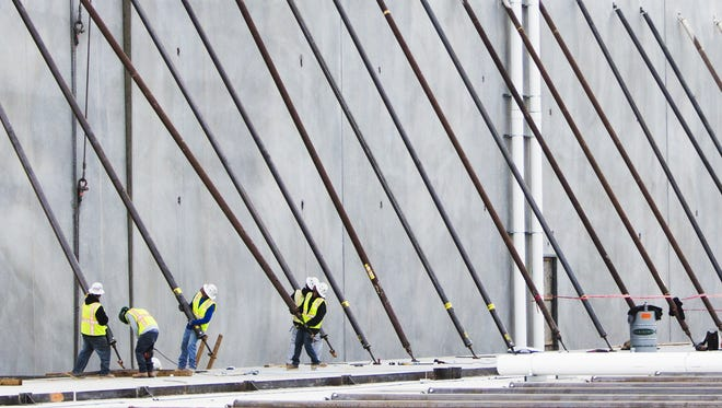 Workers install one part of a wall for the new Workers install one part of a wall for the new Conair company building in Glendale on Dec. 20, 2016.