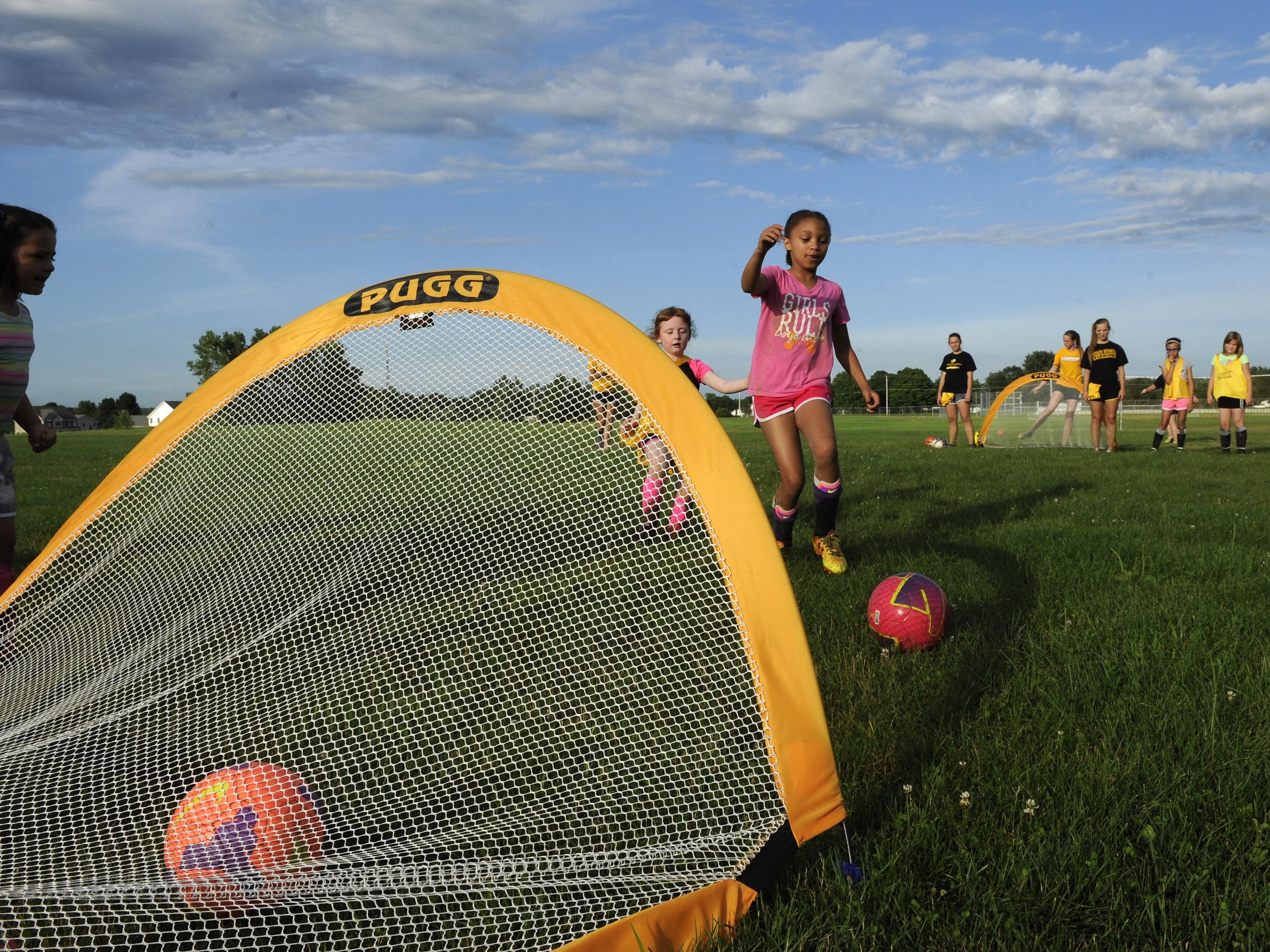 Vanuatu Hook, 6, and Taylor Brown, 8, play 1-on-1 during a youth soccer camp Monday at Watkins Memorial.