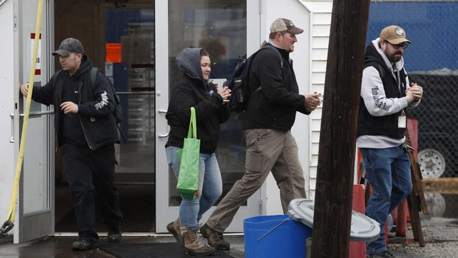 Workers rub their hands with hand sanitizer as they leave Bath Iron Works in Bath, Maine. Workers at one of the Navy's largest shipbuilders overwhelmingly voted to strike, rejecting Bath Iron Works' three-year contract offer Sunday and threatening to further delay delivery of ships.