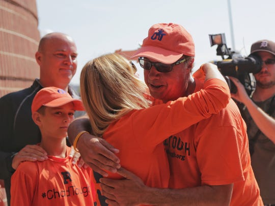 Jim Burns of Souderton, PA hugs Tammi Carr as her son CJ Carr and husband Jason Carr look on as Burns makes the end of his 600-mile walk from Philadelphia to Ann Arbor to raise awareness for ChadTough Foundation at Michigan Stadium in Ann Arbor on Monday July 11, 2016.