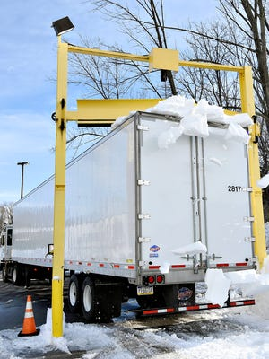 A semi-trailer is pulled through a scraper beneath a pusher blade which helps to remove snow from the roof at York Container Company in York, Pa. on Thursday, Jan. 28, 2016. The U.S. Senate is considering a bill that would allow police to issue fines to trucking companies that fail to adequately remove snow and ice from the tops of their vehicles. (Dawn J. Sagert - The York Dispatch)