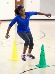 Chanel Riviere, 11, of Bear navigates through cones during a healthy eating and exercise class at the Bear-Glasgow Family YMCA.