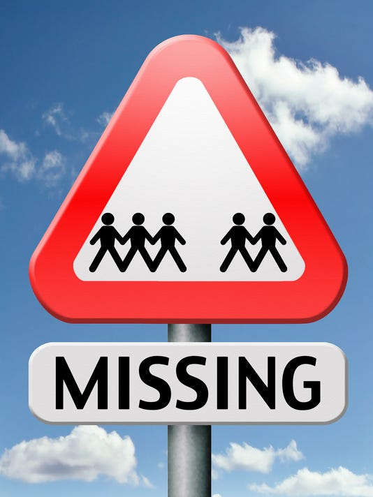 Triangle sign with people figures underneath saying missing