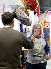 Julie Woolsey, a first-grade teacher at Fowler Elementary School, is presented a set of balloons by Associate Superintendent Peter Griffiths after she was announced as an IDEA grant winner Nov. 18 in her classroom.