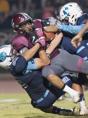 Redwood's Alonzo Ozuna (66) tackles Mt. Whitney's Israel San Miguel in last season's Cowhide football game. The Pioneers host Rangers this year for the 63rd annual Cowhide game.