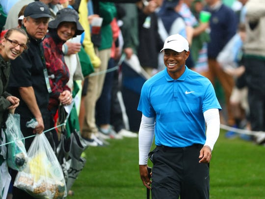 Apr 7, 2018; Augusta, GA, USA; Tiger Woods smiles as he walks to the 8th tee during the third round of the Masters golf tournament at Augusta National Golf Club.