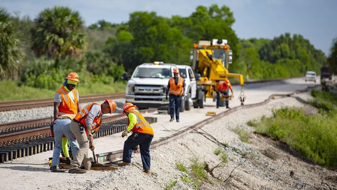 Brightline construction crews position a rail north of Hood Road in Palm Beach Gardens, Friday, August 7, 2020. Brightline is adding a second set of tracks for their planned expansion to Orlando. Construction at railroad crossing next week will close down Indiantown Road in Jupiter and Blue Heron Blvd in Riviera Beach.