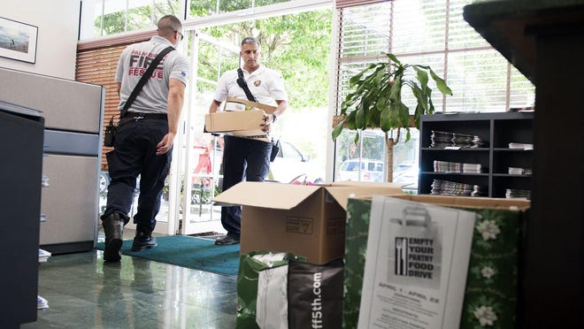 Palm Beach Fire Rescue Lt. Alex Mahy, right, and firefighter/medic Patrick Frawley carry in donated food for the Empty Your Food Pantry Drive at The Palm Beach Daily News office in 2019. CROS Ministries is one of the charities that the Town of Palm Beach United Way is helping during the coronavirus pandemic.