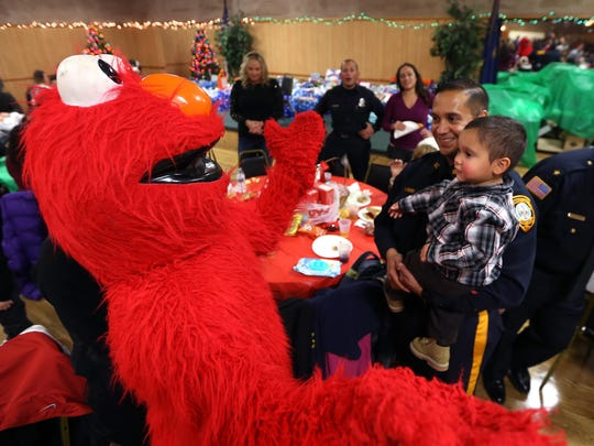 Somerset Sheriff officer Adrian Romero looks on as his son, Aries, 2, is about to get a hug from Elmo as the Italian American Police Society of New Jersey hosts their annual Big Brothers and Sisters of New Jersey Children's Christmas Party at the Whippany American Legion Hall. December 19, 2015, Whippany, NJ.