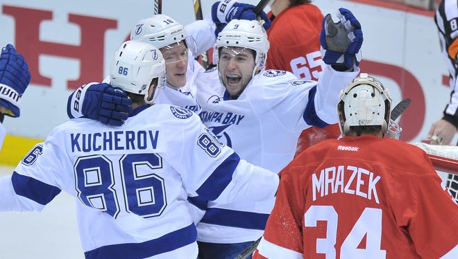 Tyler Johnson celebrates with teammates Nikita Kucherov and Ondrej Palat in front of  Wings goalie Petr Mrazek after Johnson's goal in the first period.