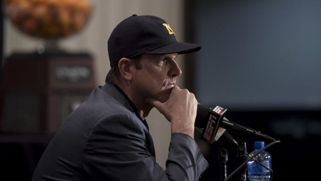 University of Michigan head football coach Jim Harbaugh answers questions on Thursday during a press conference in Fort Lauderdale.