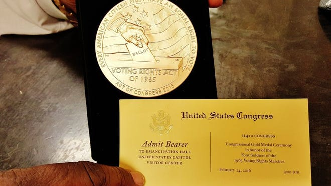 Rev. Dr. Harold Middlebrook shows the reverse side of the Foot Soldiers for Justice Congressional Gold Medal that was presented on Feb. 24, 2016, and his invitation to the ceremony.
