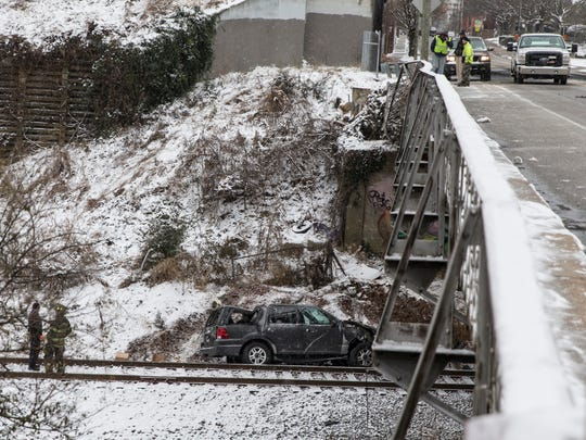 An SUV traveling Wednesday, Jan. 17, 2018 on Lombardy Street in Richmond, Va., hit a patch of ice, slid through a railing and fell off an overpass onto some train tracks below, a Richmond police officer said on the scene.